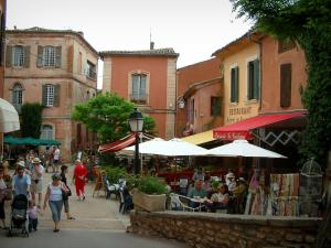 Roussillon - Square with terraces of cafés, parasols and houses with ochre facades