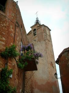 Roussillon - Belfry (tour) and red ochre house with a small balcony decorated with flowers