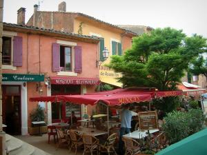 Roussillon - Square with restaurant terraces, parasols and houses with ochre facades