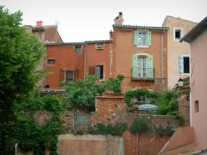 Roussillon - Houses with ochre facades and trees in the village