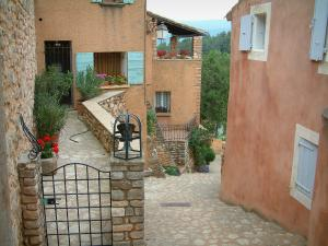 Roussillon - Sloping narrow street with ochre houses, flowers and plants