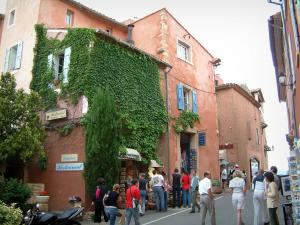Roussillon - Street with houses of red ochre colour and shops