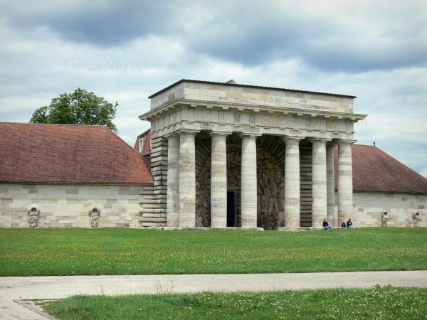 Royal saltworks of Arc-et-Senans - Guards' building (entrance to the former saltworks) with its columns; lawns dotted with flowers, path and heavy sky