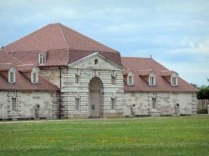 Royal saltworks of Arc-et-Senans - Building of the former royal saltworks and lawn dotted with flowers