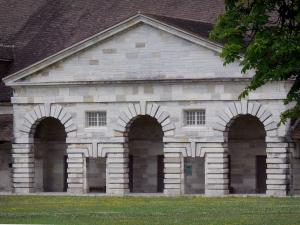 Royal saltworks of Arc-et-Senans - Portico with arches of a building of the former saltworks and a lawn dotted with flowers