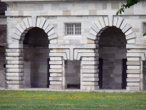 Royal saltworks of Arc-et-Senans - Arches of the portico of a building of the former saltworks and a lawn dotted with flowers