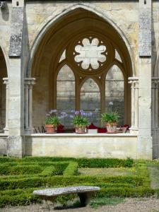 Royaumont abbey - Gothic cloister and its French-style formal garden with a bench; in the town of Asnières-sur-Oise; in the Oise-Pays de France Regional Nature Park
