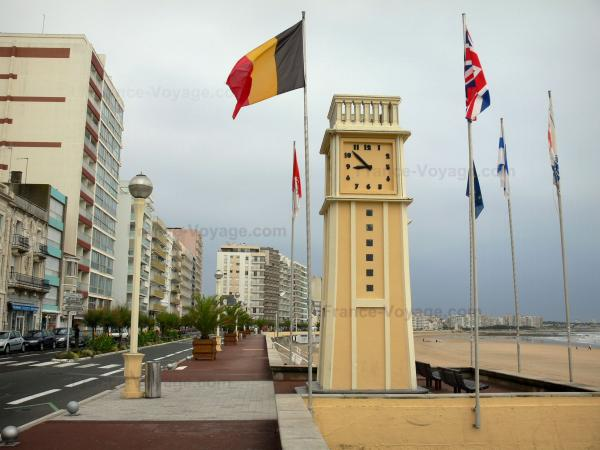 Les Sables-d'Olonne - Elevation, clock tower, flags, walkway decorated with palm trees, street, buildings and sandy beach of the seaside resort