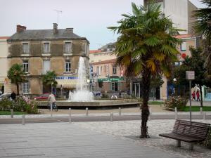 Les Sables-d'Olonne - Bench, palm tree in foreground, square with a fountain and rosebushes (roses), and houses of the town centre