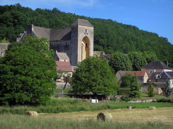 Saint-Amand-de-Coly - Fortified abbey church, houses of the village, straw bales in a field and trees, in Black Périgord