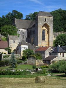 Saint-Amand-de-Coly - Fortified abbey church, houses of the village, straw bale in a field and trees, in Black Périgord