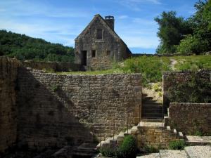 Saint-Amand-de-Coly - Ramparts (surrounding wall) of the abbey church and the small stone house, in Black Périgord
