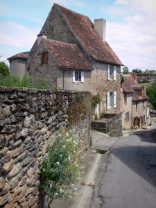 Saint-Benoît-du-Sault - Sloping street and houses of the village, stone wall in foreground