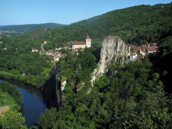 Saint-Cirq-Lapopie - Lapopie rock, trees, forest, church and houses of the hilltop village dominating the River Lot, in the Lot valley, in the Quercy