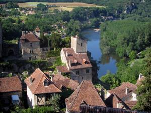 Saint-Cirq-Lapopie - Rignault museum and houses of the hilltop village dominating the River Lot and trees along the water, in the Lot valley, in the Quercy