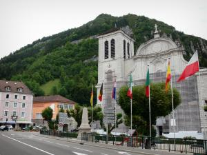 Saint-Claude - Saint-Pierre cathedral, flags, street, buildings and trees; in the Upper Jura Regional Nature Park