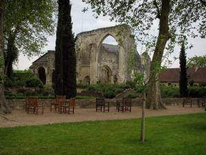 Saint-Cosme priory - Remains of the church, trees, wooden chairs and lawn of the garden