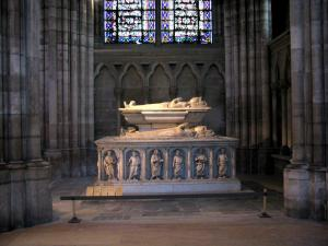 Saint-Denis basilica - Inside of the royal basilica (royal cemetery): tomb with funeral sculptures and stained glass windows in background