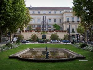 Saint-Étienne - Facade of the town hall and the Jean-Jaurès square with its pond lined with lawn, flowers and trees