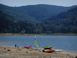 Saint-Ferréol lake - Shore with catamarans, pond and hills covered with trees