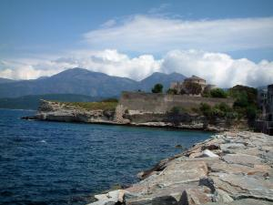 Saint-Florent - Sea, ramparts of the Genoese citadel, hills and clouds in background