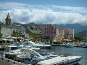 Saint-Florent - Marina with boats, church bell tower and houses of the seaside resort