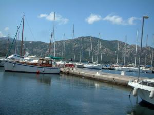 Saint-Florent - Sailboats of the marina and hills in background
