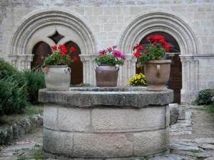 Saint-Gilbert abbey - Flower-bedecked well and bays of the chapter house of the Saint-Gilbert Neuffonts abbey; in the town of Saint-Didier-la-Forêt