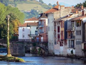 Saint-Girons - Facades of houses along the water, bridge spanning River Salat, trees, and Couserans hill in background