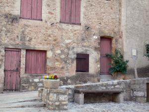 Saint-Guilhem-le-Désert - Facade of a house, bench and flowers in jar