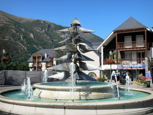 Saint-Lary-Soulan - Spa town and ski resort: fountain, houses of the village and mountains; in the Aure valley