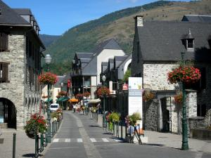 Saint-Lary-Soulan - Spa town and ski resort: street of the village lined with houses, shops and lampposts with flowers ; in the Aure valley