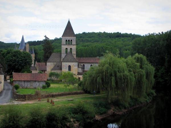 Saint-Léon-sur-Vézère - Romanesque church, Vézère river, bank, weeping willow trees along the water, houses of the village, the Clérans castle and the forest in background, in Périgord
