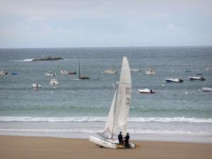 Saint-Lunaire - Seaside resort of the Emerald Coast: catamaran on the sandy beach, boats and sailboats on the sea