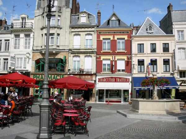Saint-Quentin - Cafe terrace, flower-bedecked fountain, shops and facades of houses in the Rue Croix Belle Porte street
