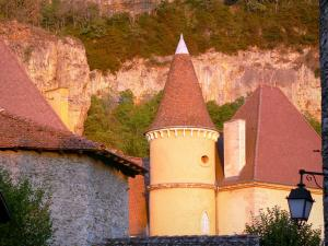 Saint-Sorlin-en-Bugey - Stone house, tower of the castle, wall lantern, and cliff in background