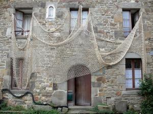 Saint-Suliac - Facade of a stone house decorated with a fishing net