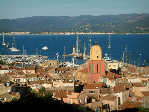 Saint-Tropez - View of the church bell tower, the roofs of the houses in the old town, the port, the boats and sailboats, the Mediterranean Sea and the hills