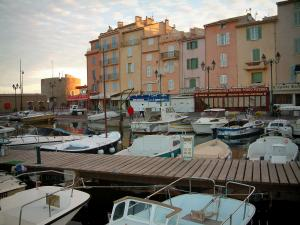 Saint-Tropez - Boats in the port, quay, restaurants, houses with colourful facades and the Portalet tower, clouds in the sky
