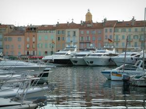 Saint-Tropez - Boats and yachts in the port with view of houses with colourful facades and the church bell tower
