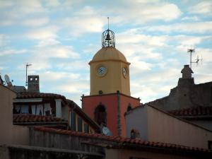 Saint-Tropez - Church bell tower with bright colours, houses of the old town and clouds in the blue sky