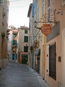 Saint-Tropez - Narrow street of the old town, houses with colourful facades decorated with shop signs