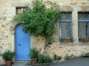 Sainte-Suzanne - Facade of a stone house with its blue door and floral ornaments