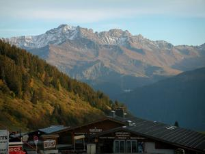 Les Saisies - Chalets of the ski resort, forests and mountains with snowy tops