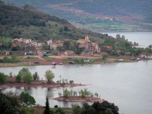 Salagou lake - Shores of reservoir, village of Celles, red cliff and trees