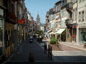 Sarrebourg - Shopping street with shops, houses and church bell tower in background