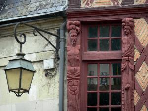 Saumur - Lamppost and wooden characters carved on the facade of an period house