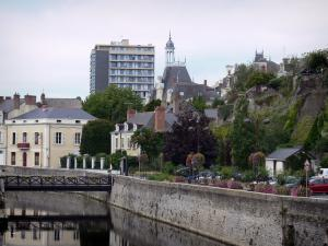 Segré - Bridge spanning the River Oudon, flower-bedecked bank, roof of the Town hall topped by a cupola, houses and buildings of the city