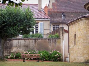 Semur-en-Brionnais - Garden featuring a bench, a tree and flowers, the Saint-Hilaire collegiate church and houses of the village; in Brionnais
