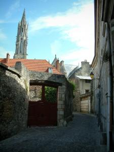 Senlis - Paved street of the ancient city with a portal, houses and tower of the Notre-Dame cathedral with its spire (Gothic architecture)